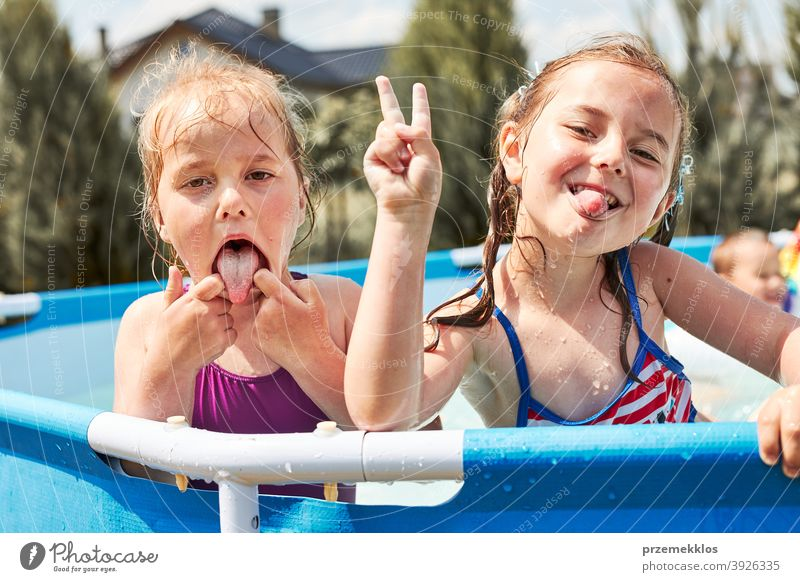 Happy girls making V sign gesture silly face playing in a pool authentic backyard childhood children family fun garden happiness happy joy kid laughing