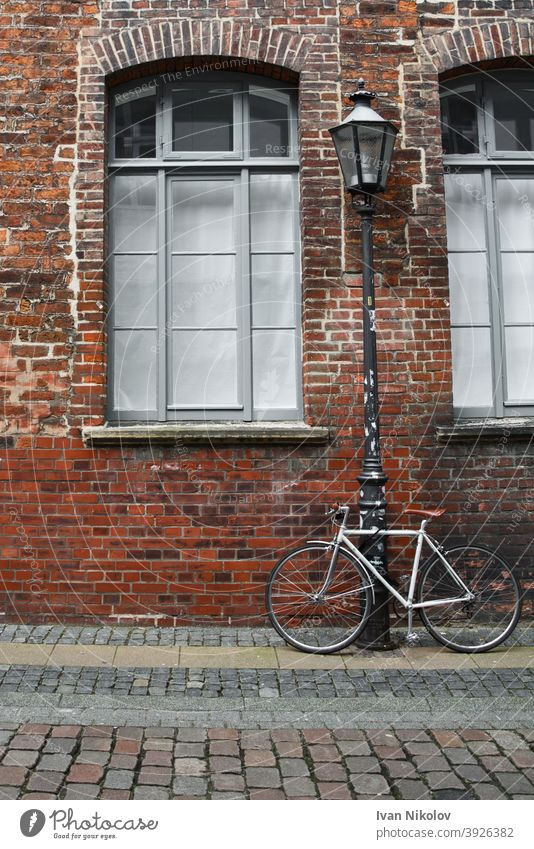 White bicycle tied to a streetlamp in front of a brick wall bike background retro vintage laterne architecture europe european facade germany house outdoor