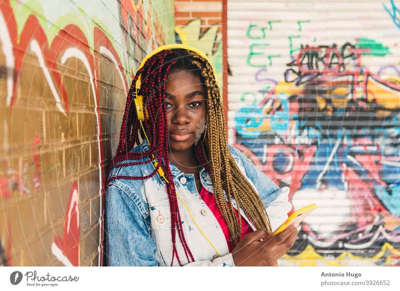 Exotic black girl with colored braids in her hair and yellow headphones listening to music on her cell phone. Leaning on a graffiti wall. mobile cellular exotic