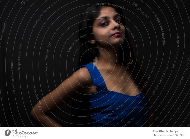 Fashion portrait of an young and attractive Indian Bengali brunette girl with blue western dress in front of a black studio background. Indian fashion portrait and lifestyle.