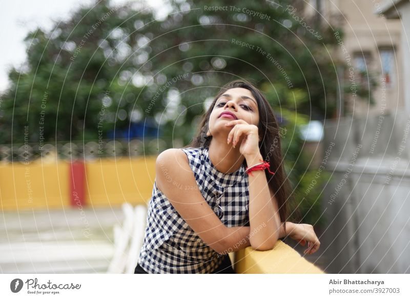 Portrait of a beautiful and young Indian Bengali brunette girl in western dress leaning on the side of rooftop in the afternoon with a tree full of yellow flowers in background. Indian lifestyle