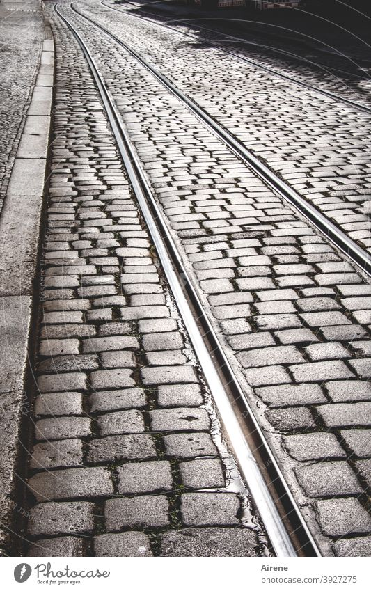 always on the rails Street Cobblestones tram tracks Right ahead straight Deserted Gray paved sunny Pedestrian precinct Paving stone railway tracks