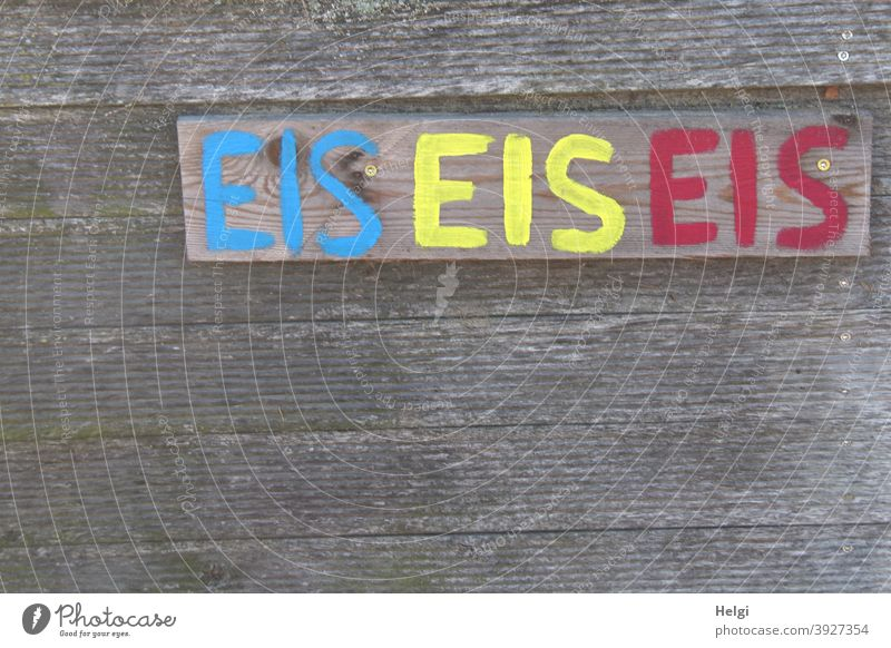 EIS EIS EIS - The word EIS handwritten in blue, yellow and red on a board on a wooden wall Ice Word Letters (alphabet) writing Handwriting Advertising