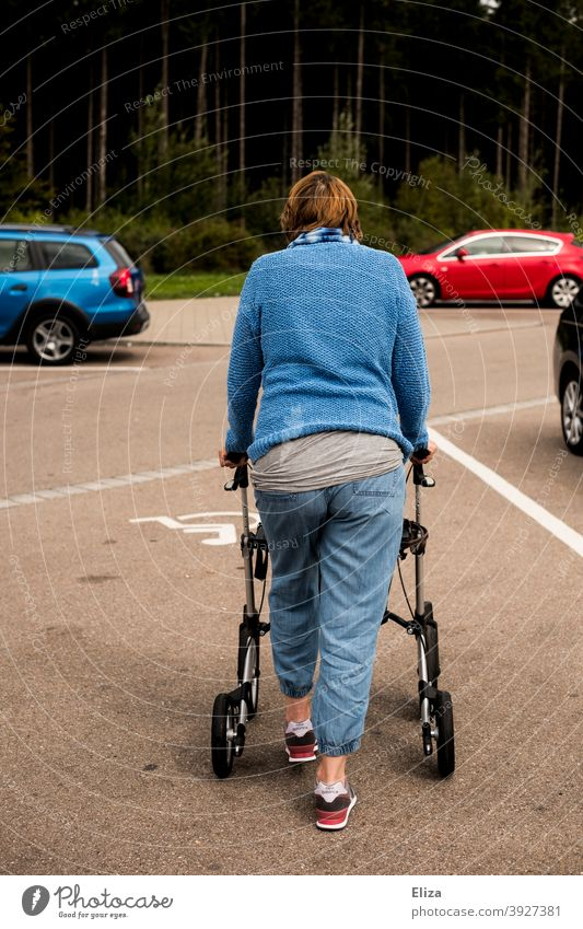 A woman with a walking disability pushes her walker across a disabled parking space walking impediment handicap Woman Human being Rollator Handicapped Mobility