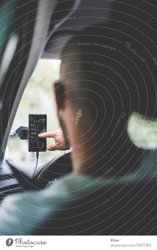 Man sitting in car typing something into his cell phone Cellphone Typing Navigation Bracket Mobile phone cradle mobile phone smartphone Motoring while Driving