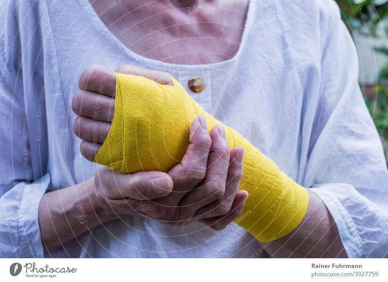 A woman has an injury on her wrist, she wears a yellow bandage violation Bandage Healthy Illness Accident at work absenteeism health insurance person Woman