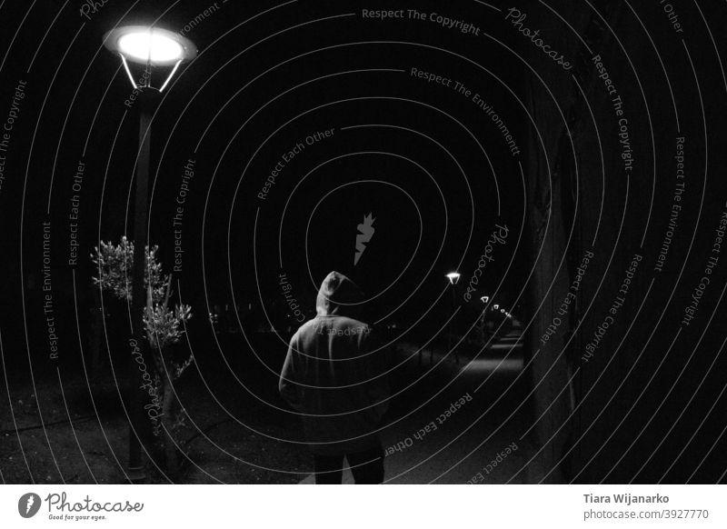 Man in the street boy male Street streetlamp Shadow Light Night Night life Night shot Dark Loneliness Emotions Sadness alone Hooded (clothing) Black Monochrome