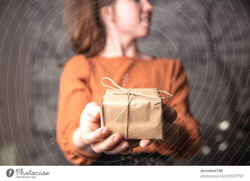 Young female holding a small craft paper gift box, plain brown paper for recycle and present. Birthday, Valentines concept christmas package ribbon holiday