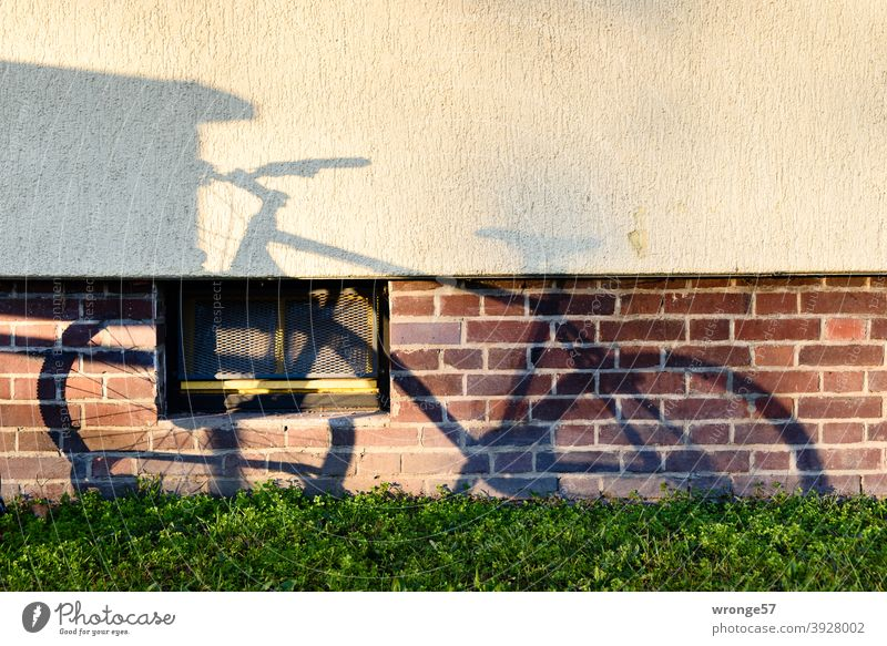 Shadow image of a bicycle standing in a bicycle stand on the wall of an apartment building Shadow play shadow cast Bicycle Mountain bike mtb Wall (building)