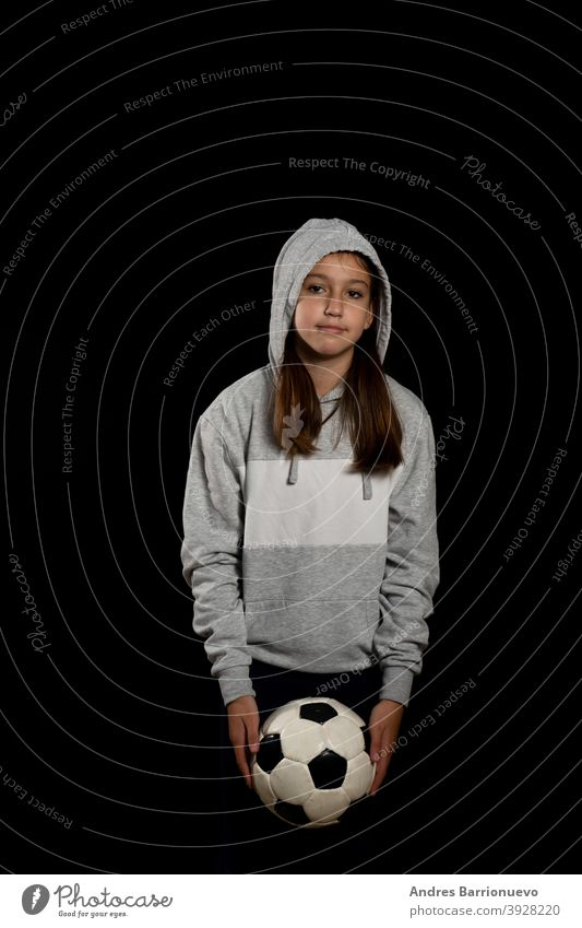 Little girl in gray sweatshirt and two pigtails playing with a soccer ball isolated on black background sport eye cut lifestyle joy beauty player young healthy