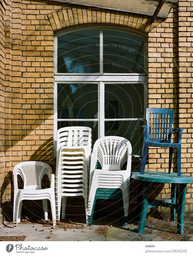 several stacking chairs made of plastic are stacked on top of each other against a house wall Chair Stack Sunlight Exterior shot Colour photo Arrangement