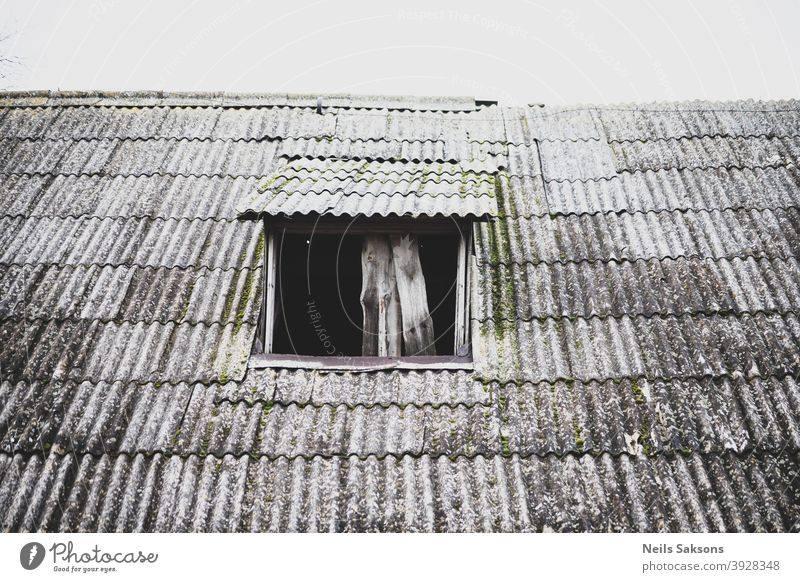 crooked wavy slate roof of old barn with roof window without glass Abstract aged architecture asbestos background built ceramic construction cover detail dirty