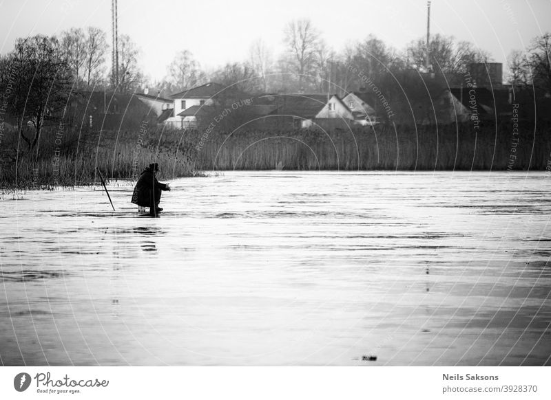 lonely fisherman on thin 5 cm ice. ice fishing is dangerous hobby. traditions in Latvia. Leisure and hobbies Catch Lake Lakeside Exterior shot River thin ice