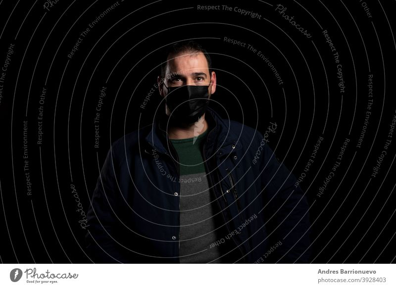 Bearded man equipped with a mask to protect himself from coronavirus wearing a blue jacket posing isolated on black background guy health stylish hand