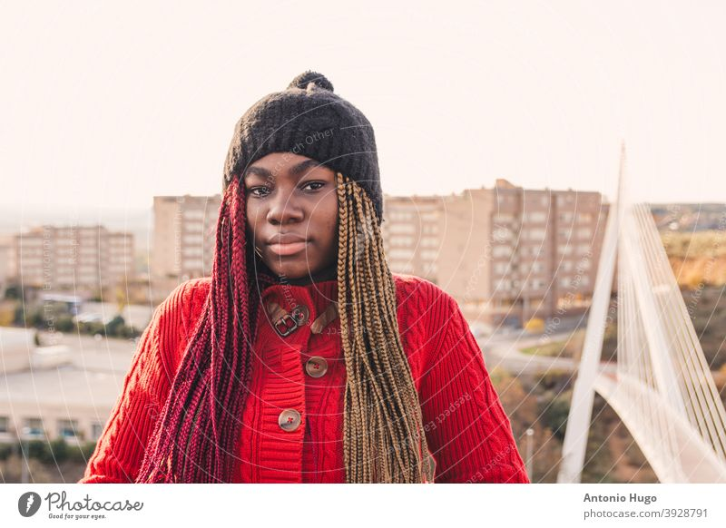 Portrait of a black girl with colored braids. Dressed in a red sweater and a black wool cap. Urban bridge and buildings in the background. urban exotic portrait