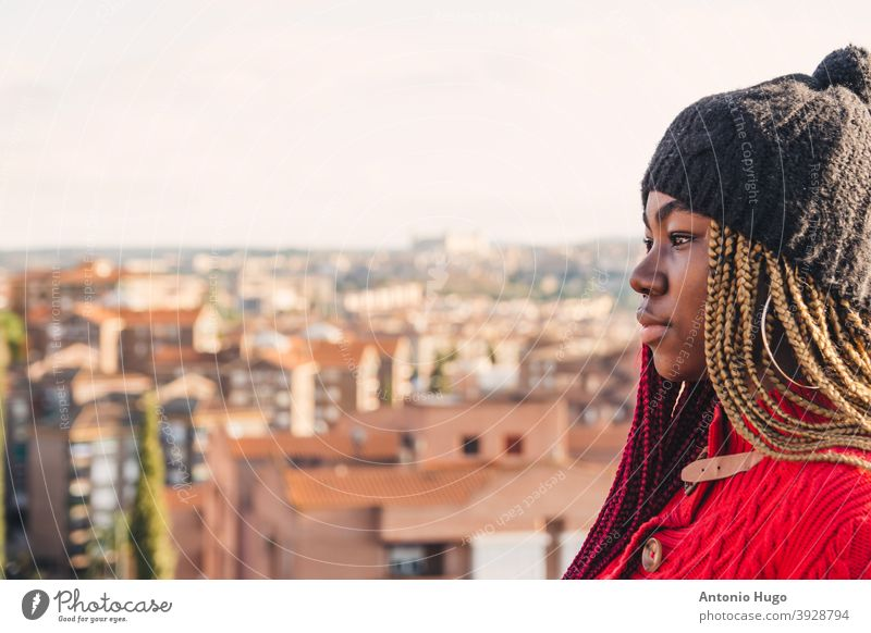 Portrait of a black girl with colored braids. Dressed in a red sweater and a black wool cap. City view in the background. urban bridge buildings exotic portrait