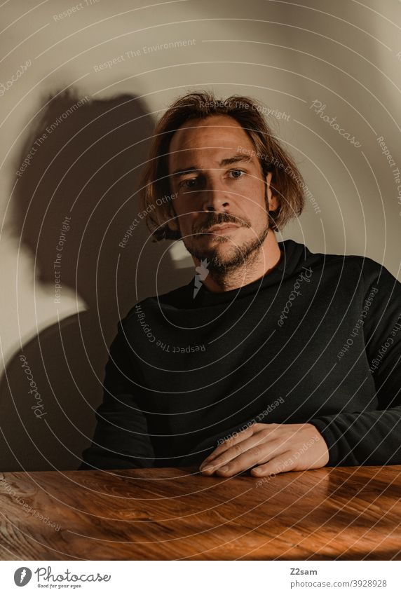 Portrait of a young man portrait Young man Sweater honestly atmospherically Wooden table Facial hair Moustache sincerely Modern fashionable naturally relaxed