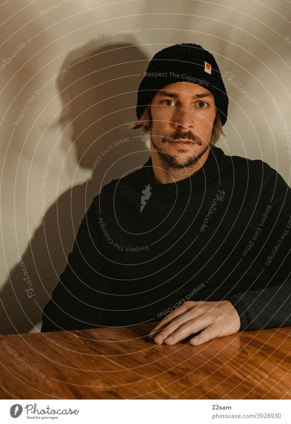 Portrait of a young man portrait Young man Cap Sweater honestly atmospherically Wooden table Facial hair Moustache sincerely Modern fashionable naturally