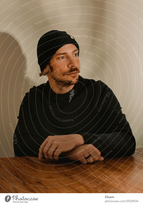 Portrait of a young man with warm colouring portrait Cool Cap Sweater Facial hair Face Human being Colour photo Wooden table Man Young man hip Future