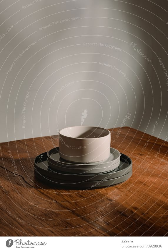 Dishes atmospherically arranged on the table Crockery Product photography stillife Plate bowls Wooden table Table warm colors Light lightning bolt Sunlight