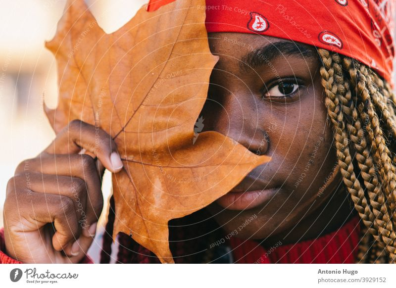Portrait of a black girl with colored braids covering her eye with a tree leaf. Autumn time. bandana autumn artistic autumnal headscarf denim jacket vintage