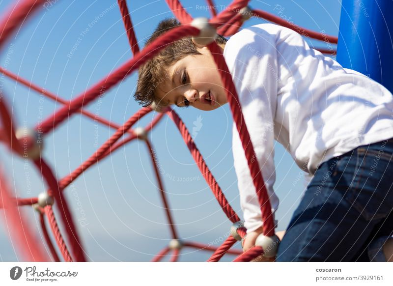 Funny boy climbing in a playground active activity adventure balance blue sky brave caucasian child childhood children climbing frame color colorful enjoying