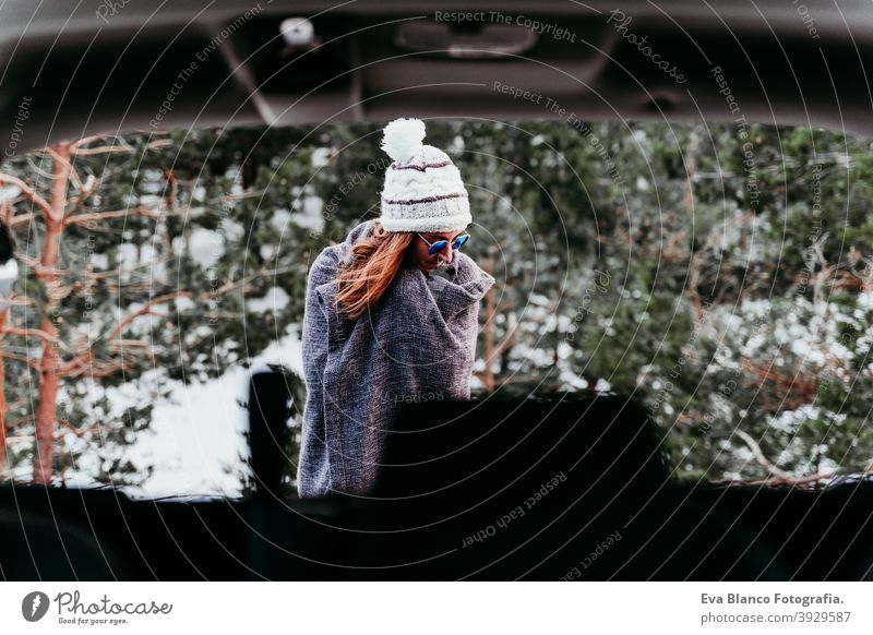 back view from inside a car of young woman outdoors wearing stylish hat. Winter season. snowy mountain background winter enjoy nature leisure green weather