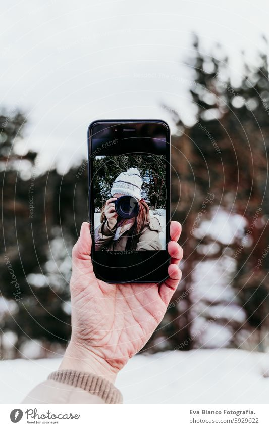 woman taking picture to mobile phone, selfie. Techonolgy and lifestyle. Snowy mountain background camera technology outdoors winter cold city wall yellow