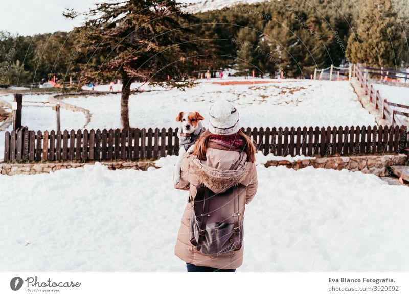 woman and cute jack russell dog enjoying outdoors at the mountain with snow. winter season holding shoulders love kiss hug travel lifestyle wanderlust traveling