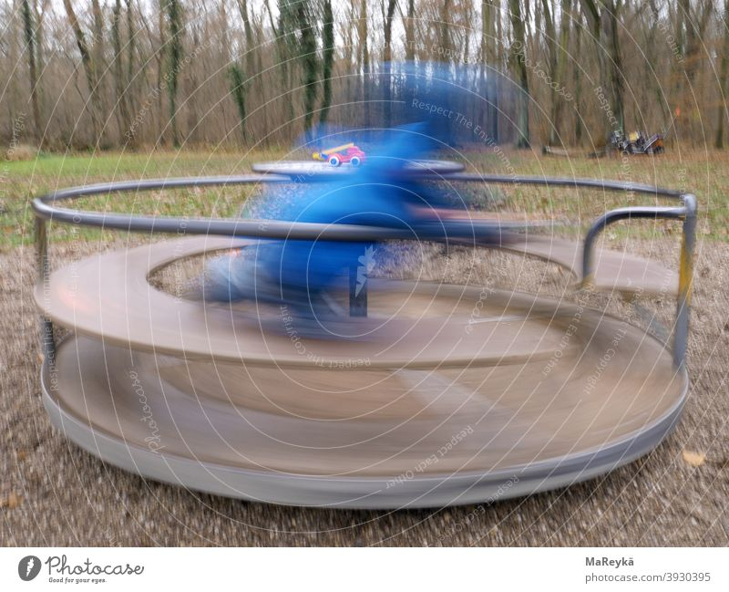 Kid spins on turntable in the forest playground and gets a spinning worm Rotate Potter's wheel Fire engine Playing woodland playground Playground Long exposure