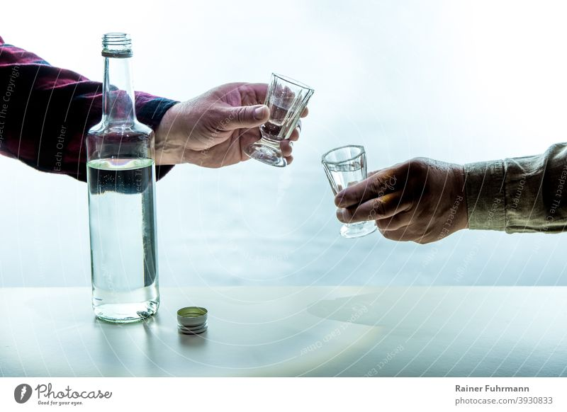 On a table there is a bottle with alcohol. The hands of two men are holding shot glasses. They toast with each other. Alcoholic drinks alcoholism Addiction