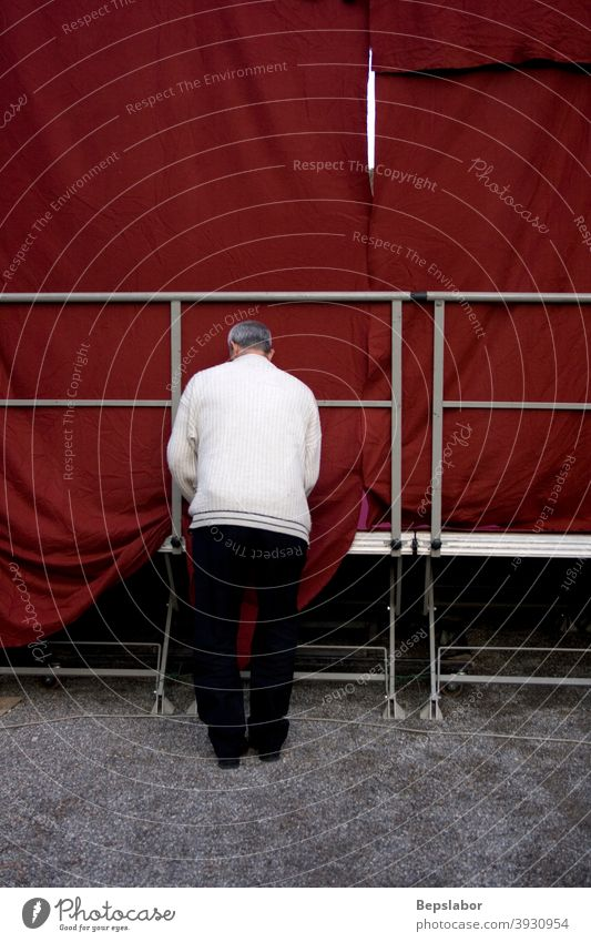 Man arranges the red marquee of the conference stage man worker ceremony working people fix care perfectionist behind