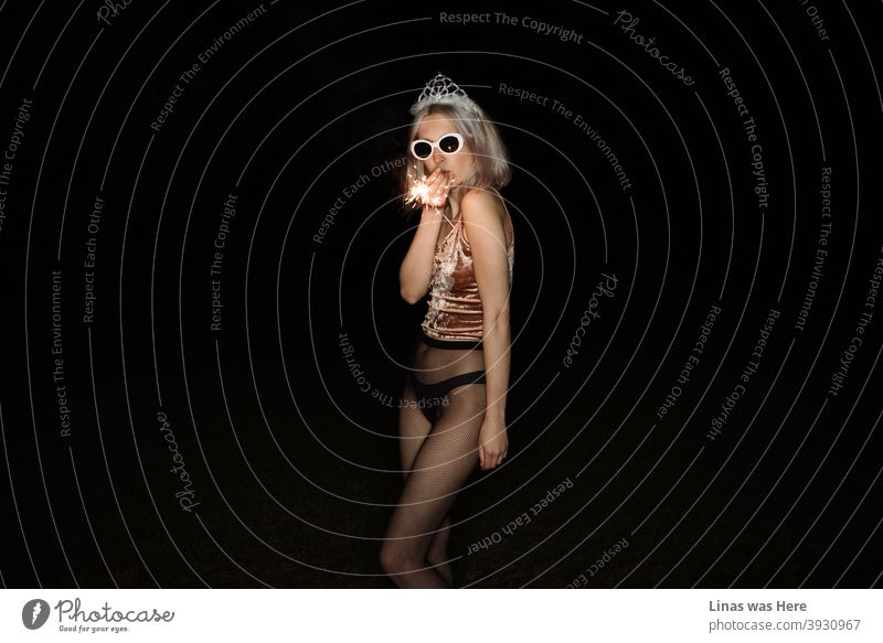 It's party time and this gorgeous blonde girl is all about having fun. Dressed in black lingerie and a shiny tiara with sunglasses she is ready to celebrate. Darkness is all around and only the flash reveals the secrets of the night.