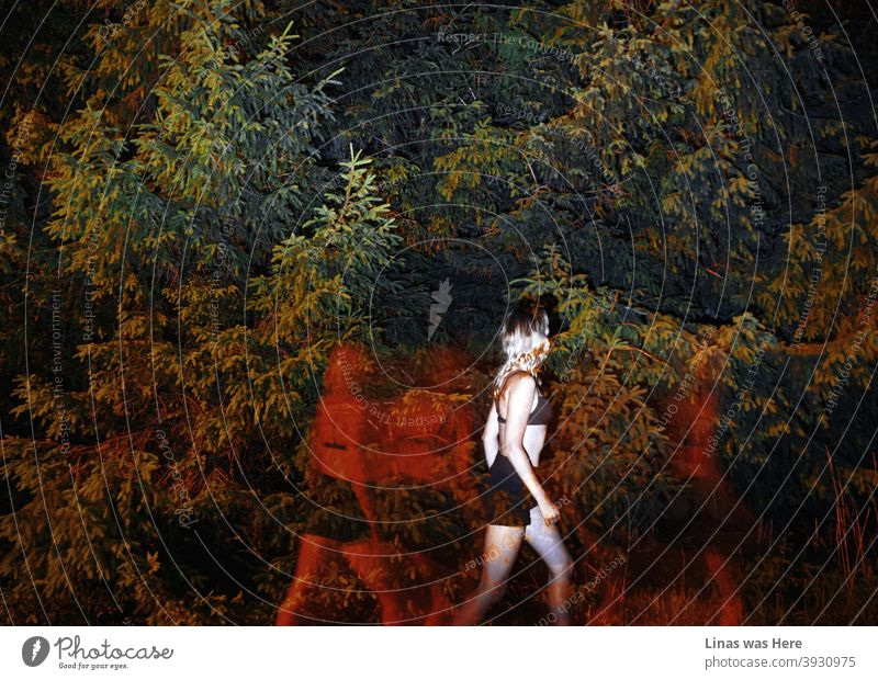 Dark shadows with red lights are following this gorgeous blonde girl. The lingerie model is dressed in black shorts and a bikini. She is walking away from invisible ghosts. It's all happening in dark woods.