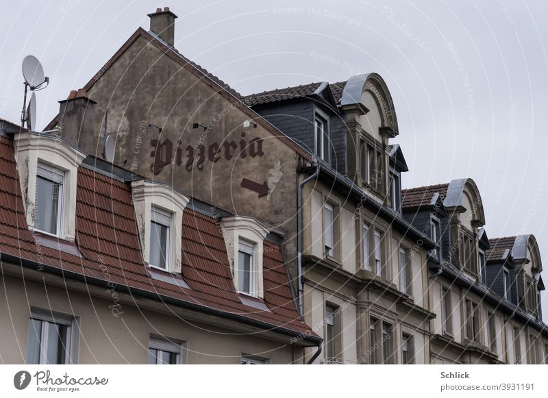 Text Pizzeria in squiggly writing and arrow down to the entrance on an old house gable pizzeria house gables House (Residential Structure) Old Arrow Direction
