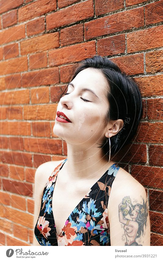 sensual woman leaning on brick wall girl tattoo nice beauty cool hipster cute dark hair young nature lifestyle people human portrait poses fashion tattooed