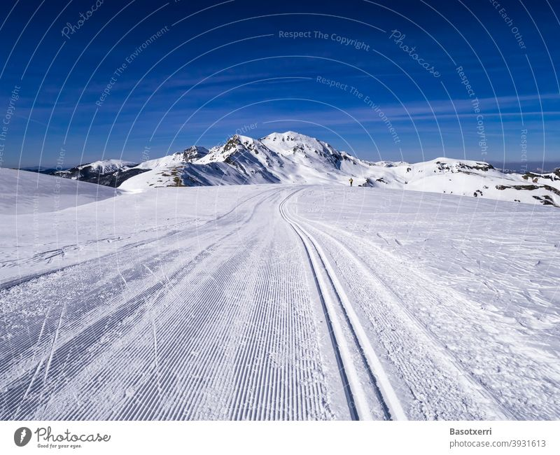 Traced cross-country skiing track in the mountains. Small person (cross-country skier) in the background. Isaba/Belagua, Navarra in the Spanish Pyrenees.