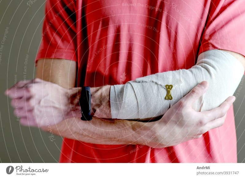 The man supports the injured hand. Primary care, the hand is tightly fixed with an elastic bandage. background training arm person doctor sprain cast joint