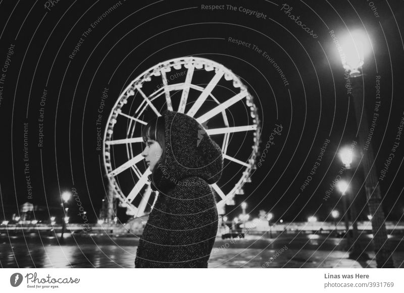 Paris at night is a beautiful thing. Even on such a cold autumn night. A pretty girl is wearing a coat and her profile aligns well with the Ferris wheel. The Black and white image is moody and nostalgic in a way. A lonely girl in an empty big city.