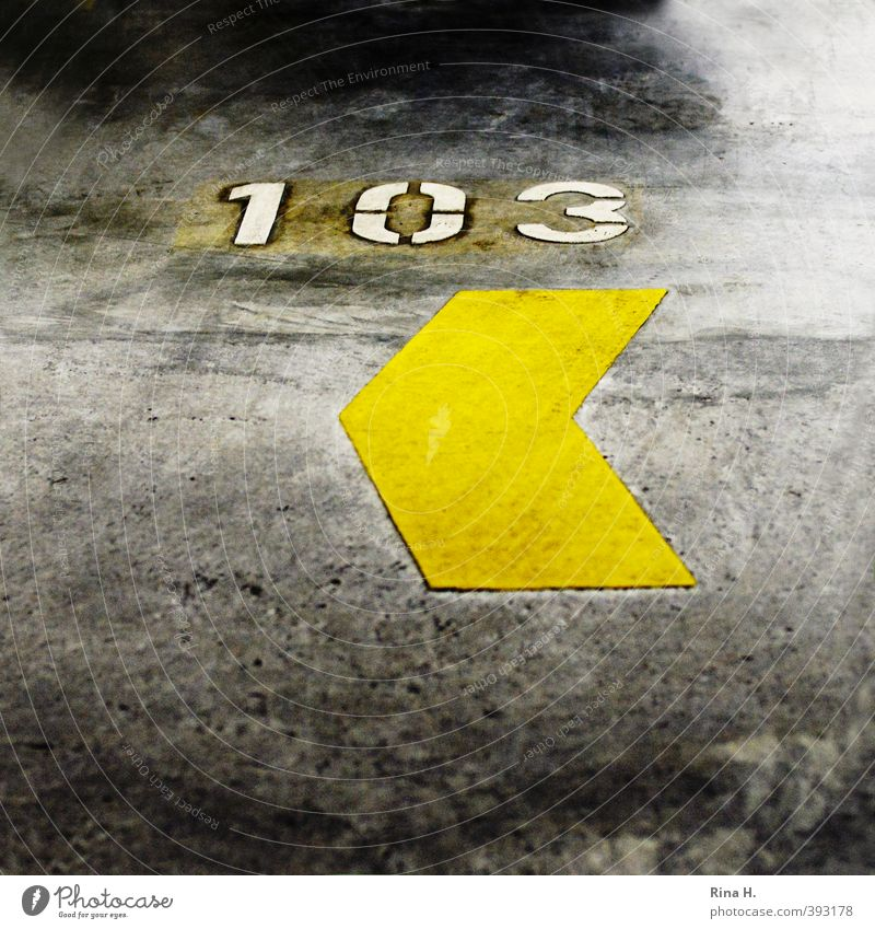 <103 Parking garage Arrow Authentic Yellow Concrete Digits and numbers Square Signs and labeling Parking space number Colour photo Interior shot Deserted