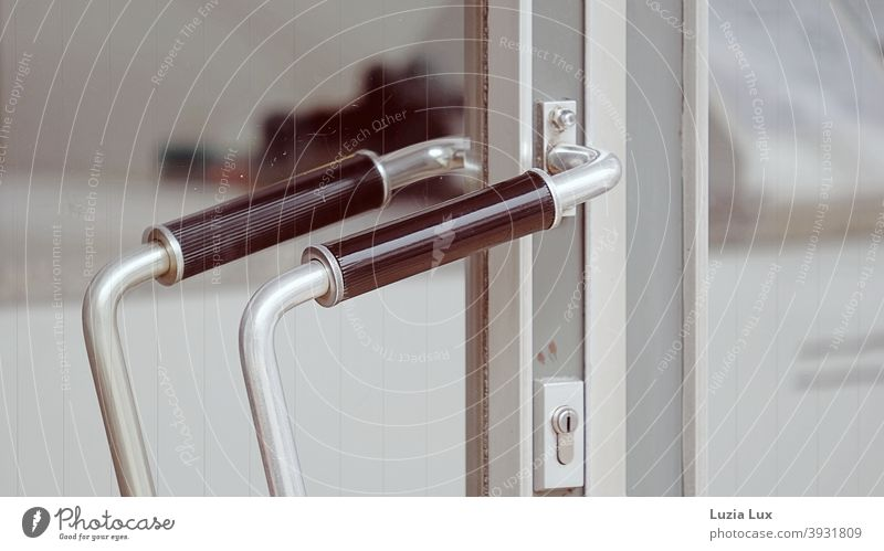 An old-fashioned shop door with a graceful handle bar, in delicate colours Door handle Handlebar Load Store premises daintily Old fashioned Curved Closed Trade