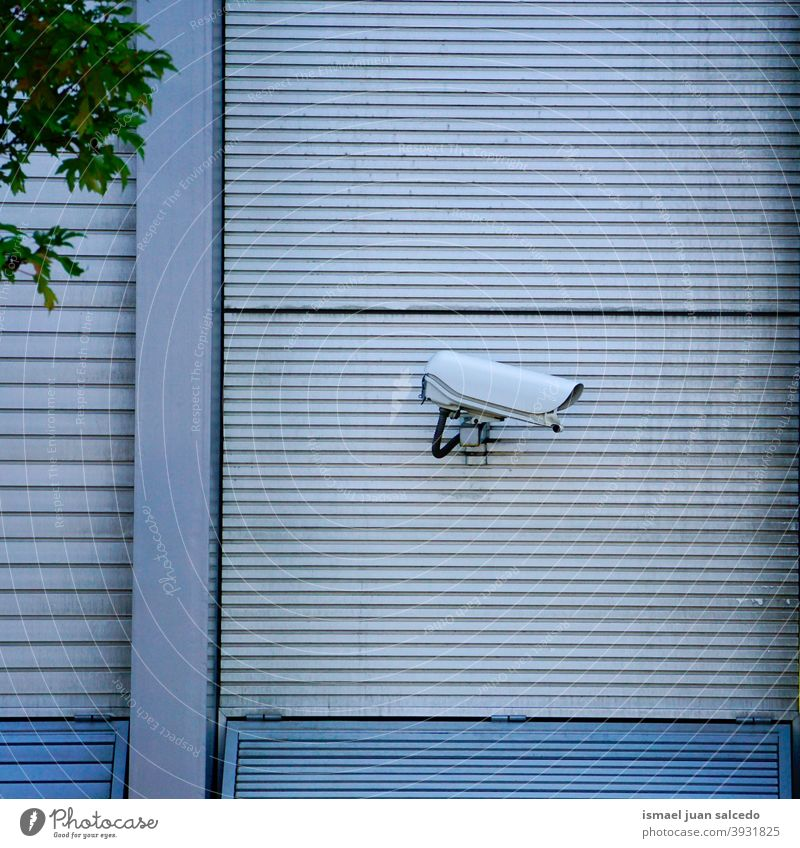 security camera on the wall of the building video camera background street surveillance equipment safety protection technology system control guard watching