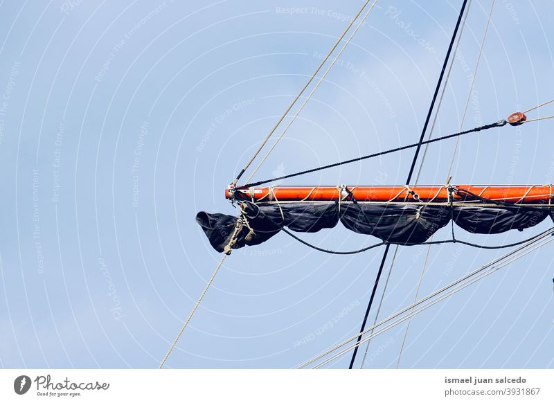 sailboat mast, sail and rope ship sailing rigging vessel sea seaport tall nautical transportation sky blue masts ropes old travel marine water wind wood yacht