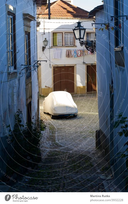 Anonymous car under cover on a narrow cobbled street. anonymous empty tarp tarpaulin old cobblestone white houses laundry line lanterns travel alone Off-Season