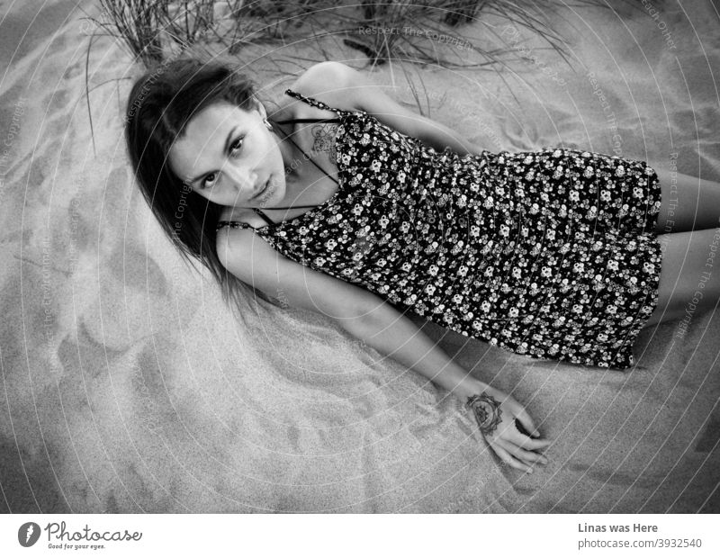 A wonderful brunette model dressed in a light dress is lying on the sand. Even though the image is black & white, it is obvious that she is perfectly tanned while enjoying the summer sun. Her big black eyes are staring right into the camera.
