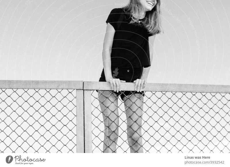 Happy girl is climbing a fence on a perfect summer day. Big smile, long legs, and black outfit. A throwback to warmer and happier days. black and white happy