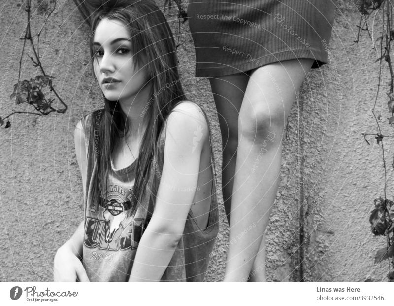 A gorgeous brunette model is looking straight into the camera. Her big black eyes are going straight through anything. Also, other models' legs are right next to this beauty in the composition.