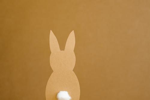A paper Easter bunny on a yellow brown background Easter Bunny Paper silhouette Low-cut Handicraft Pushtail Hare ears rabbit Easter decoration Yellow Brown