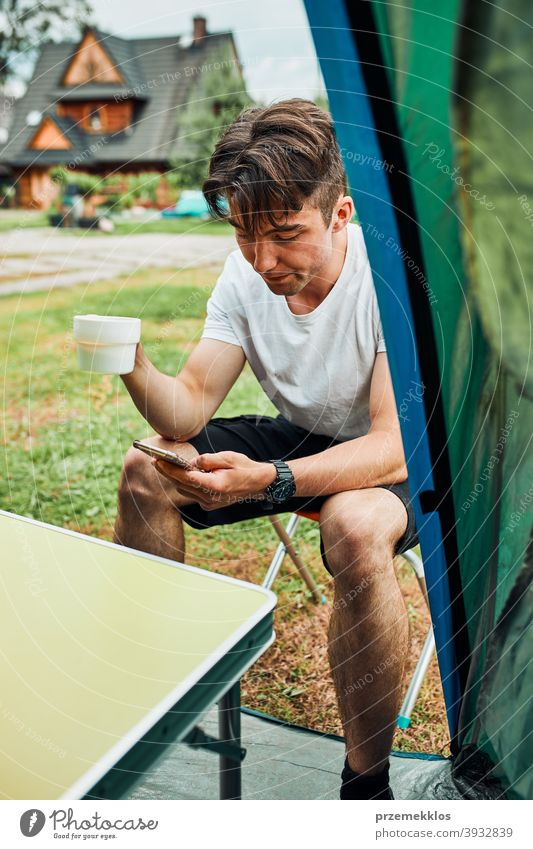 Young man drinking a coffee sitting at front of tent in the morning adventure beverage break breakfast camp camping closeup cup exploration freedom hiker hot