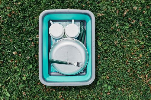 Washing up bowl filled with the washed outdoor dishes, plates, cups and cutlery put on grass camp camping campsite cleaning cleanup dish wash dish washing life
